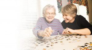 Elderly Woman And Younger Woman Doing Puzzle Gradient