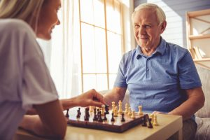 Volunteer Playing Chess With Senior