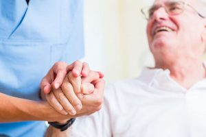 Nurse Holding Hand Of Senior Man