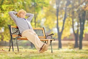 Senior Gentleman Sitting On A Bench And Relaxing In Park