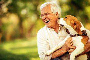 Senior man smiling holding dog