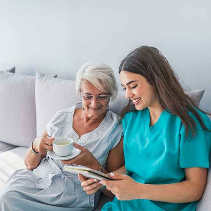 At Home Aide Reading With Loved One