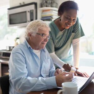 At Home Aide With Elderly Man On Computer