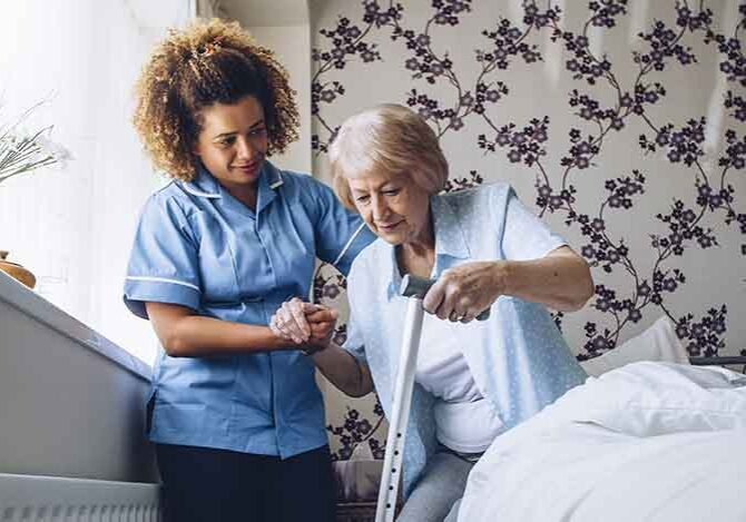 At Home Aide Helping Elderly Woman Out Of Bed